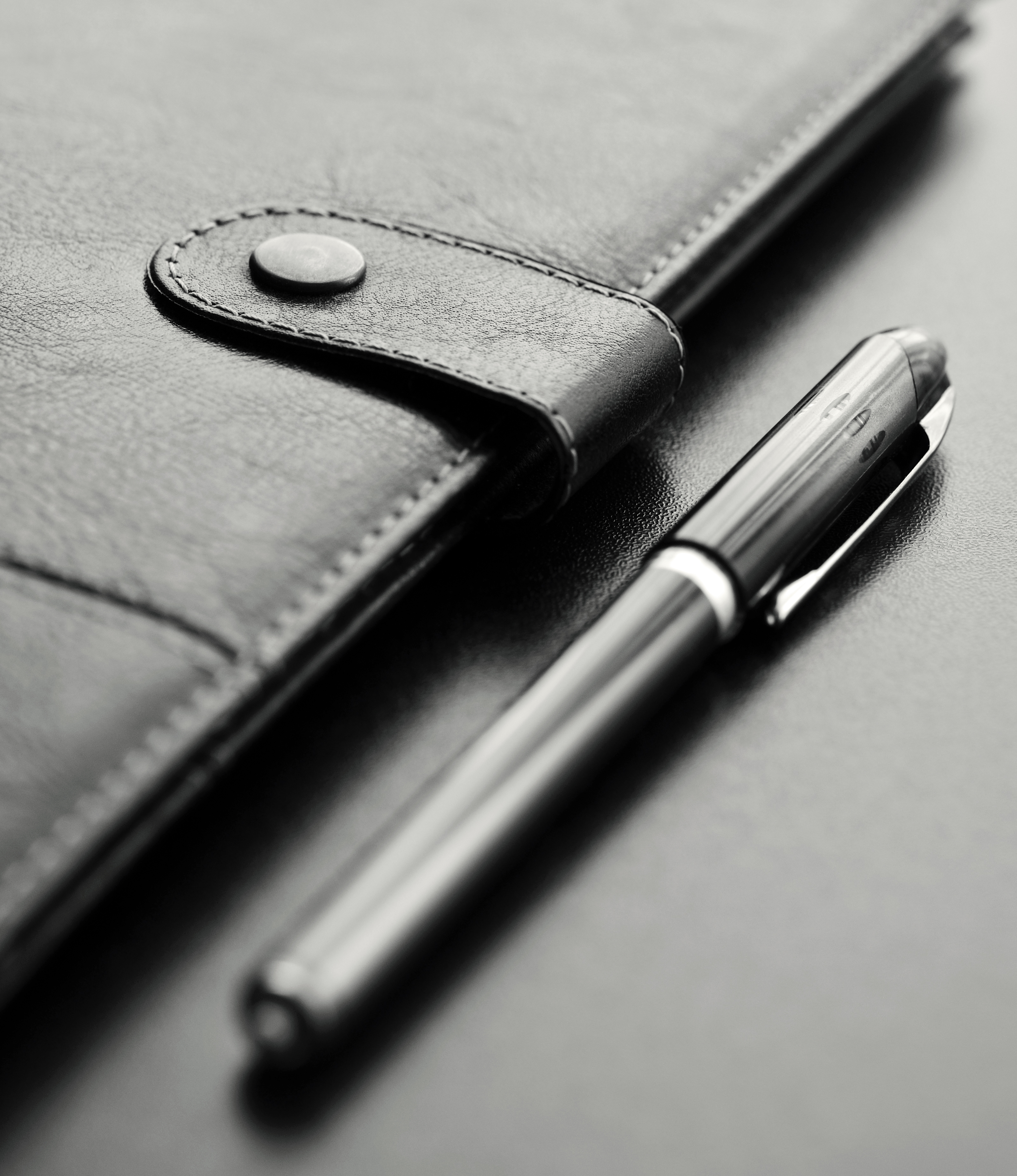 Close-up of a black personal agenda and with a pen with selective focus