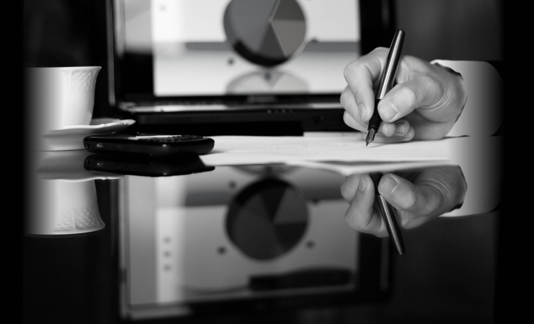 black and white image of a man writing with a fountain pen